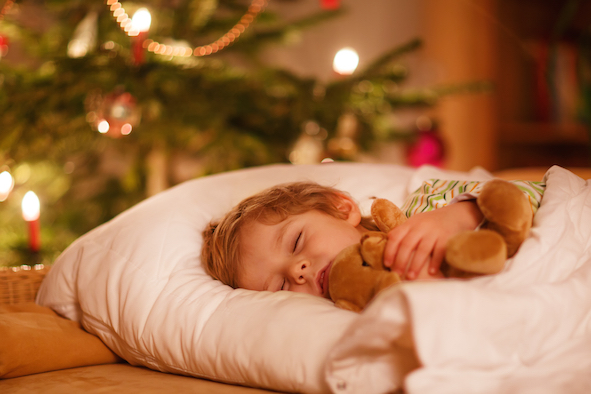 Little cute blond boy sleeping under Christmas tree and dreaming of Santa at home indoors